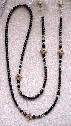 THIS IS ONE OF MY BEST SELLING CHAINS. IT IS DONE WITH CELTIC KNOTS THAT ARE GOLDPEWTER WITH BLACK CZECH GLASS BEADS AND EMERALD AND AURUM(GOLD) SWAROVSKI CRYSTALS. IT IS APPROX 29 LONG. IT IS STRUNG ON 49 STRAND NYLON COATED WIRE THAT IS VERY FLEXIBLE AND NON KINKING. IT RETAILS FOR $48 IN Boho Jewelry, Beaded Jewelry, Jewelery, Beaded Necklace, Jewelry Design, Beaded Lanyards, Eyeglasses, Swarovski Crystals, Bracelets