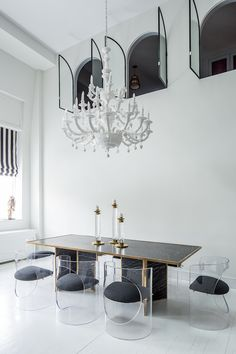 Amazing two-story dining room features a trio of arched windows accented with glass doors alongside white chandelier illuminating black dining table with gold trim surrounded by lucite dining chairs with black seats situated in front of window dressed in black and white striped roman shade atop white plank floors.