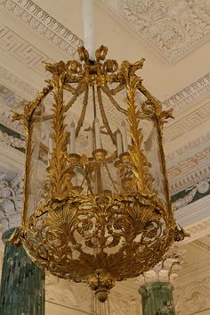 """The Grecian Hall is noted for its many fine bronzes, such as a clock stamped """"L. J. Laguesse"""", candelabra with sculptural groups, vases and fire-dogs of perfect design. Exquisite in shape, chasing and gilding are the bronze lanterns."""