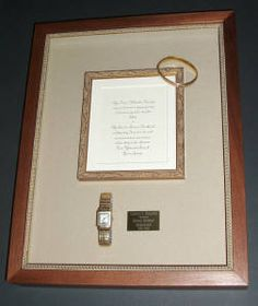 Our client's grandparents' 1919 wedding invitation, gold watch and bracelet shadowboxed on linen.  Fashioned a form from acrylic for the watch and sewed the gold bracelet in place. The plaque is what's engraved on the back of the watch in the same font. Solid walnut frame with a lambs tongue fillet and glazed with Museum Glass. We love creating family heirlooms!  www.GildedLilyFraming.com