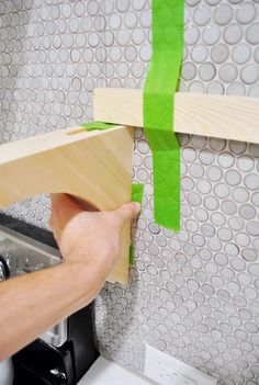 How To Hang Brackets On A Tiled Wall - excellent info & lots of tips to keep in mind when hanging open shelving + how wood shelves were finished off with trim moulding,  wood filler & paint.