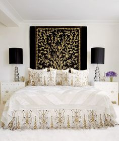 Feminine, patterned bedroom with black and gold art, matching table lamps, and purple flowers