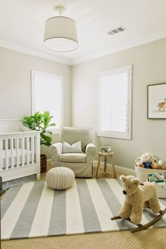 Modern neutral nursery design featuring a white, beige, and gray color palette featuring a white drum shade ceiling fixture, cream walls, white trim, a white crib, beige slipcovered chair, knit pouf, stuffed rocking bear, animal nursery art print, and a gray and white striped area rug over tan sisal carpeting - Neutral Nursery Ideas & Decor
