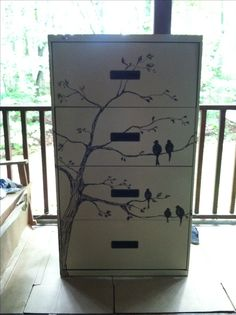 Found this $20 black filing cabinet at Goodwill.  It was in great working order so I gave it a facelift with an oil based almond paint applied with a roller (one best for smooth surfaces) and drew on the tree and birds (birds representing my family) with an oil based Sharpie.