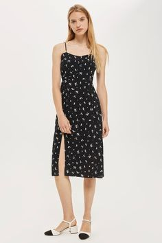 This pretty black and white floral print midi dress is just as suited to summer days as it is to winter layered over a basic tee and tights. It features skinny straps and a cheeky skirt split.