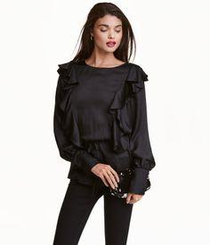 Sort. Bluse i tynd, vævet kvalitet med let glans. Blusen har flæser både på for- og bagstykket. Lange ærmer med bred manchet og lukning. Er skåret i taljen