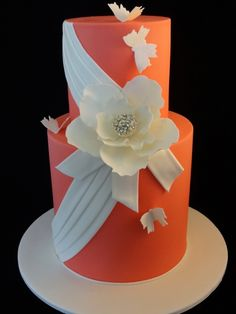 Tall tiered orange cake with ivory flower, butterflies and draping