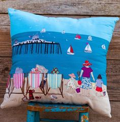 'A Day on The Beach Cushion'. This wonderful statement cushion is created by hand cutting all the fabric pieces and then adding all the definition and detail by free-hand machine embroidery. This scene depicts the quirky British beach with thermos flasks, sun hats and granny on the beach making a beautiful cushion to Brighton up a sofa or a chair.