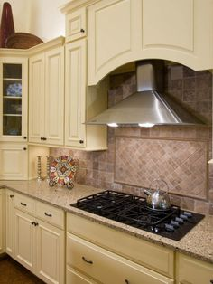 Kitchen: Stainless Steel Vent Hood In Cabin Kitchen. gas cooktop. marble countertop. white kitchen cabinet. tile backsplash. decorative dish. stainless steel hood. wall cabinet.