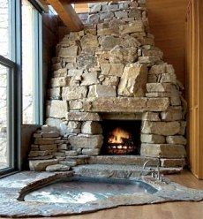 corner stacked stone fireplace and hot tub with huge floor-to-ceiling windows to left of frame.  Another picture showed a guide-rail (I guess this picture was before it was up to code?)