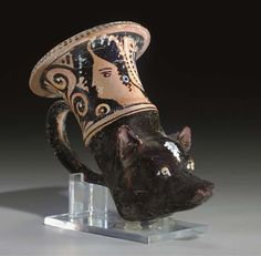 AN APULIAN RED-FIGURED RHYTON  WORKSHOP OF THE BALTIMORE PAINTER, CIRCA 330 B.C.  Molded in the form of the head of a maltese, with peaked triangular ears, a tapering muzzle and large almond-shaped eyes, a white tuft of hair at the forehead, the bowl with a female head wearing a sakkos in profile to the left, palmettes and tendrils on either side of the handle, vertical lines along the everted rim, details in added white and red  6¾ in. (17.1 cm.) long