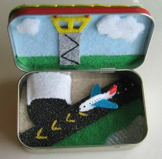 Heres an awesome little airplane play set. All in one little Altoid tin. Included in my little play set is a tiny 1 1/2 stiffened felt airplane. A control tower with little vinyl windows and shiny red seed bead lights on top.     Extra fluffy clouds made from fur felt. An airplane hanger to park the plane and two runways. (One in the altoid tin and one on top of the tin).     On the floor of the tin is a corner of blue sparkling water, a green grass area, a sandy area and of course the s...