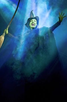 This is a photo of the Broadway play, Wicked. The blue light is cast down on the wicked witch, Elphaba, makes her seem evil and powerful. Although she is lit with colored light, her face still is rendered as being very green.
