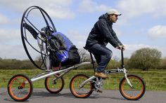 Paravelo flying bicycle - photo from visualnews; This invention includes a bicycle and a powered parachute assembly that follows behind when using the bicycle. When reassembled to pull the motor closer to the rider, and the parachute is deployed behind, the cyclist can take to the air like a paraglider. (No cliff needed.)