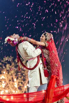 Indian Wedding : Ceremony- The bride puts the orchid flower garland around bridegroom's neck