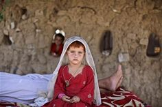 Afghan #refugee girl, laiba Hazrat, 5, sits on a bed next to her sleeping granfather, outside their home in a slum on the outskirts of Islamabad, #Pakistan.  (AP Photo/Muhammed Muheisen)