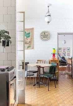 Azulejo branco, lajotas antigas e móveis vintage na cozinha desse apê em SP.