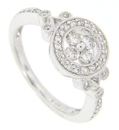 A diamond studded circle is the primary feature of this 14K white gold engagement ring. Inside the circle are set four round diamonds. Diamonds also set down the sides of the ring. A total of .42 carats total weight of diamonds can be found in the ring. Size: 6 1/4. We can re-size.