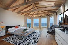 Floor-to-ceiling windows make spectacular ocean views the focal point of this modern master bedroom. Wood accents bring texture and dimension to create an elegant space, while soft gray and beige walls contrast beautifully with throw pillows and accent rugs to add a dash of color to the palette. Lots to learn from this contemporary bedroom.  #DesignEnvy #Inspired #ThatView #SanClemente #SanClementeRealEstate #EchelbergerGroup