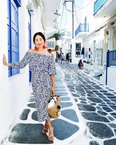 7 chic summer outfit ideas to copy from the best fashion blogger Instagrams of the week: Nicole Warne wears an off-the-shoulder printed dress and bold red tassle earrings for the perfect vacation outfit