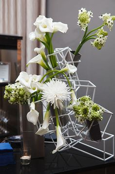 A geometric floral arrangement holds various white blooms for a modern affair.