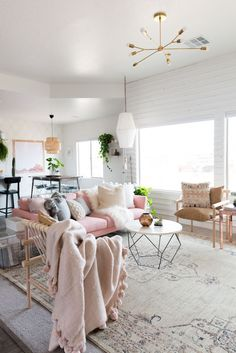 This living room is so collected and cozy! Love the pink couch, brass light and dowel chairs!