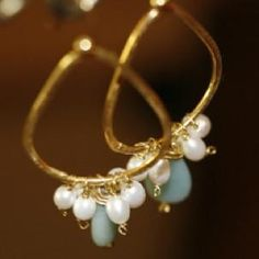 A pure piece of amazonite nestles between several freshwater pearls and hangs from a 2″ gold teardrop.