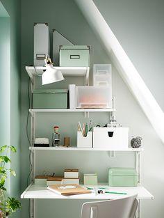 Sistema de almacenaje de pared de IKEA, con estantes de diferente ancho, debajo de un techo abuhardillado.