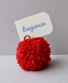 Red yarn pom pom place holders. Wedding decor - i like this