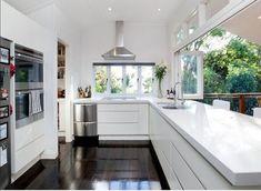 Moderní kuchyně s velkým oknem přímo na terasu pro výdej jídla.