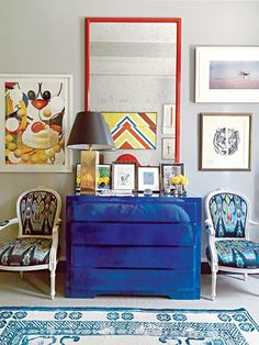The red framed mirror adds a pop of color to this eclectic wall grouping