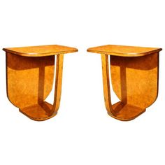 """A pair of Art Deco style console tables with rounded rectangular tops on single rectangular supports and shaped bases.  The faux bois finish simulates a burl wood.  The geometric stylization of forms inspired in part by Cubism and with a certain degree of abstraction and streamlining is the very essence of the Art Deco period.  French. CIRCA: 20th Century DIMENSIONS: 29"""" h x 27"""" w x 16"""" d"""