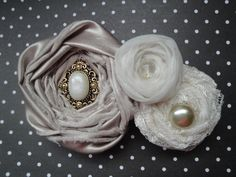 Elegant rosette cluster headband made with hand rolled satin, lace and sheer fabric. Each rose is accented with a unique embellishment and is then mounted on a stretch lace headband made to fit any age!!