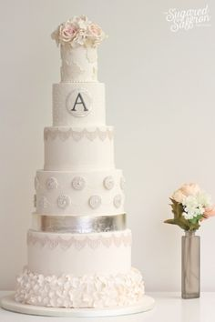 This tall wedding cake with silver  is so beautiful