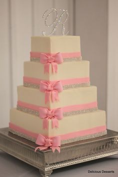 Crystal & Pink Wedding Cake - Inspired by a delicate pink bow invitation, this cake is decorated with fondant bands, gumpaste bows, & crystal bands (from Diamond Party Confetti $148.70).  It is frosted with buttercream.  Serves 154. $1070 does not include tax or delivery