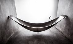 """The Vessel tub, a hammock-inspired suspended soaker tub by SplinterWorks (a UK-based sculptural furniture manufacturer) is crafted of carbon fiber, 8.85′ long, and installed with heavy-duty stainless steel wall brackets that allow it to """"hang"""" above the floor. Its insulated foam core keeps water warm for longer than typical tubs."""