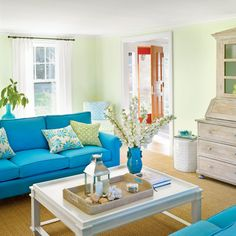 """In the living room, seafoam green walls are a fresh and unexpected backdrop for a pair of bright turquoise sofas and lively patterned throw pillows in vibrant hues. """"Blues and greens are great for a beach house,"""" says Lynn. """"They feel like summer all year"""