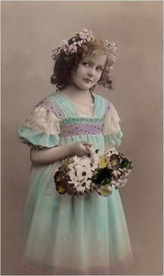 Vintage girl with basket of flowers in blue dress.