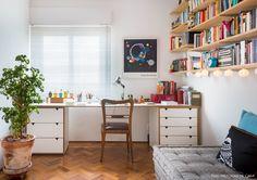 Home office integrado à sala tem prateleiras sustentadas por mãos francesas e futons.