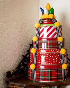 Stack thrifted cookie tins for unique holiday wrapping or as a Christmas tree by Jennifer Perkins