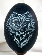 """""""Surly Cat"""" Emu Egg. No paint is involved in any of these pieces. The normal emu shell has at least three major color layers that are revealed as one cuts into them. The outside layer is usually so dark a green that it looks black. Beneath that is a teal layer and then if you go deep enough there is a very thin layer of white. It is so thin that I usually tell  my students that they have to carve it """"as if they were petting a butterfly with a feather.""""  Enjoy!"""
