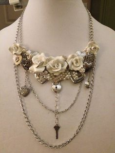 Collage of vintage pieces with polymer clay roses, chains and charms.