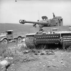 """A captured German Tiger I tank. On 12 May 1943, General Alexander wrote: """"It appears that we have taken over 1,000 guns, of which 180 are 88-mm, 250 tanks, and many thousands of motor vehicles, many of which are serviceable. German prisoners driving their own vehicles formed a dense column on the road from Grombalia to Medjez el Bab all day to-day."""""""