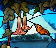 Detail from a leaded stained glass door depicting flowers floripondio and butterflies, glass painting by IKO Studio, Orvieto, Italy Particolare di porta con vetrata artistica a piombo con fiori di floripondio e farfalle, pittura su vetro a glisaglia e smalti