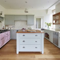 Classic, in-frame manor house kitchen. Hand painted in Farrow & Ball's Mizzle. A perfect combination with a statement Rose Aga and solid cherry island worktop and plate rack.