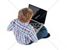 rear view of an elementary boy browsing on laptop. - Rear view of an elementary boy browsing on laptop while sitting on floor,