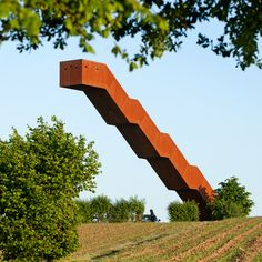 This weathering steel staircase by engineer Close to Bone cantilevers off a hill in Flanders, forming an observation tower overlooking farmland and a forest