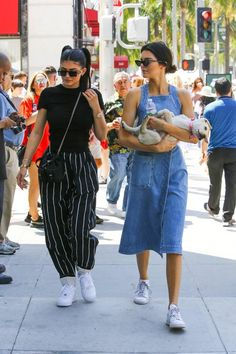 Kylie Jenner wearing Nike Air Force 1 Sneakers, Helmut Lang Cotton Jersey T-Shirt, Celine Striped Trousers, Prada Vela Mini Crossbody Backpack and Le Specs X Adam Selman the Flex Sunglasses