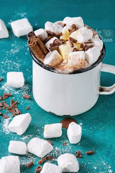 Hot chocolate with homemade marshmallow, chocolate chips, cinnamon sticks and syrup in white vintage enamel mug over bright turquoise wooden background. Close up