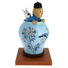 Tintin peeps out of a Chinese vase as he spies on criminals in The Blue Lotus. Painted entirely by hand, the main piece of this top-quality collectible is made out of resin. Art Lotus, Lotus Bleu, Vase Centerpieces, Vases Decor, Statues, Art Resin, Herge Tintin, Eiffel Tower Vases, Disney Figurines